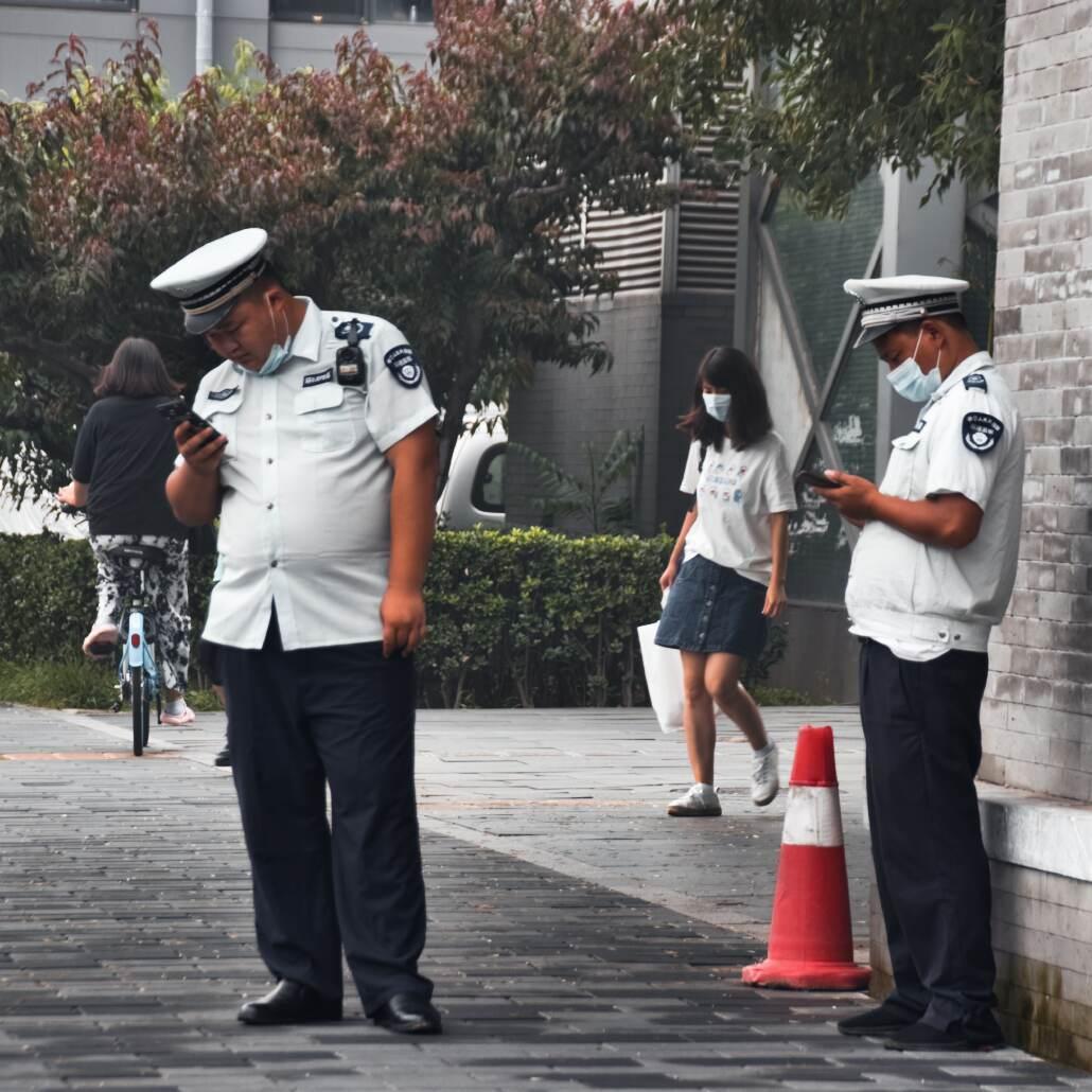 Verkehrspolizisten, die aufs Handy schauen, in Peking